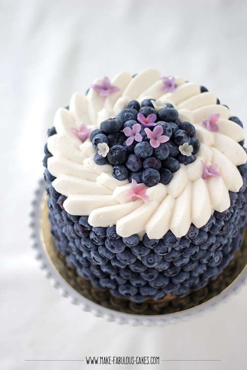 Blueberry Cream Cake with lots of  blueberries on the side of the cake